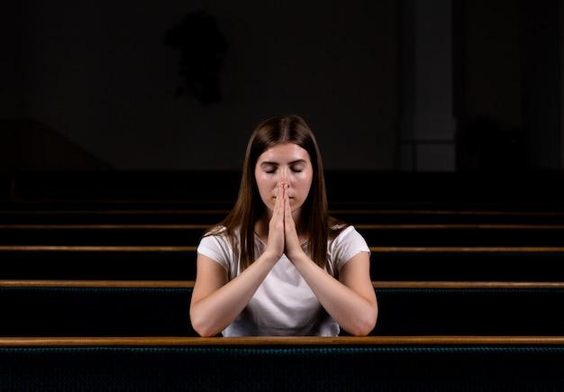 Een christelijk meisje in wit shirt zit en bidt met nederig hart in de kerk