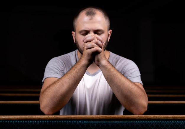 Een christelijke man in een wit shirt zit en bidt met nederig hart in de kerk