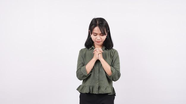 Een christelijke vrouw die nederig bidt geïsoleerde witte muur