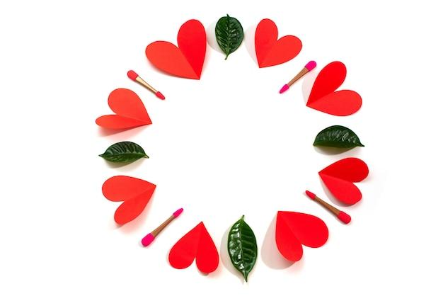 Een cirkel van rode harten borstelt voor de ogen groene bladeren op een witte achtergrond bovenaanzicht van flat lag