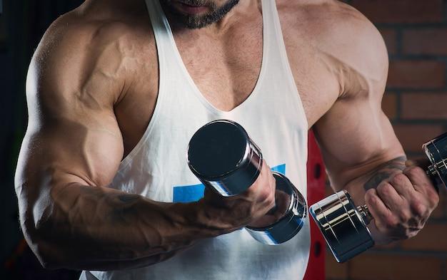 Een close foto van de armen van een bodybuilder die biceps curls met halters doet