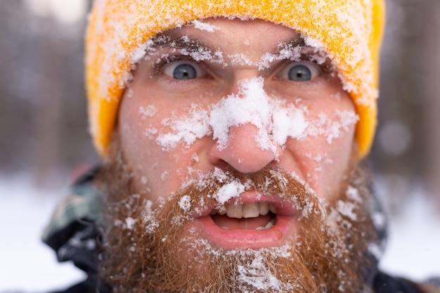 Een close portret van een man met een baard, allemaal gezicht in de sneeuw, in een besneeuwd bos