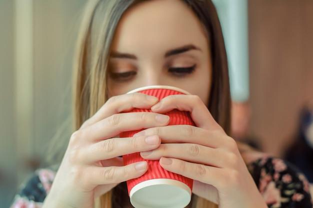 Een close-up foto van een jong meisje, zittend in een café en koffie te drinken