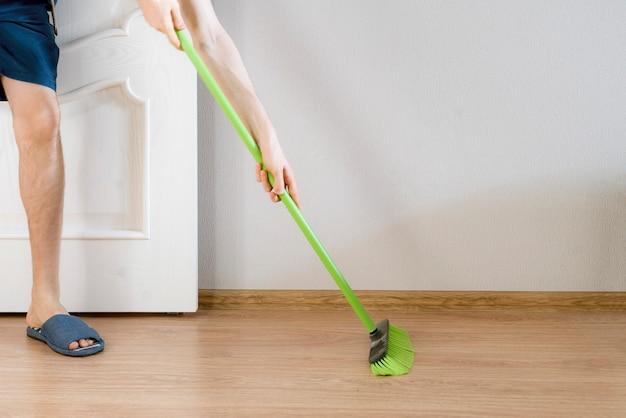 Een close-up persoon die een borstel vasthoudt en thuis de vloer schoonmaakt met een borstel