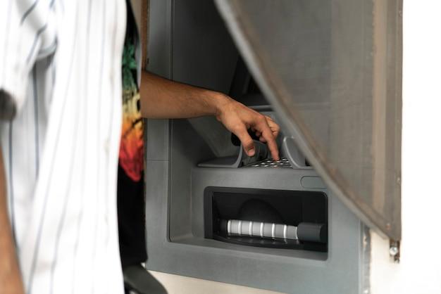 Een close-up persoon die geldautomaat gebruikt om wat contant geld van een bankkaart te nemen