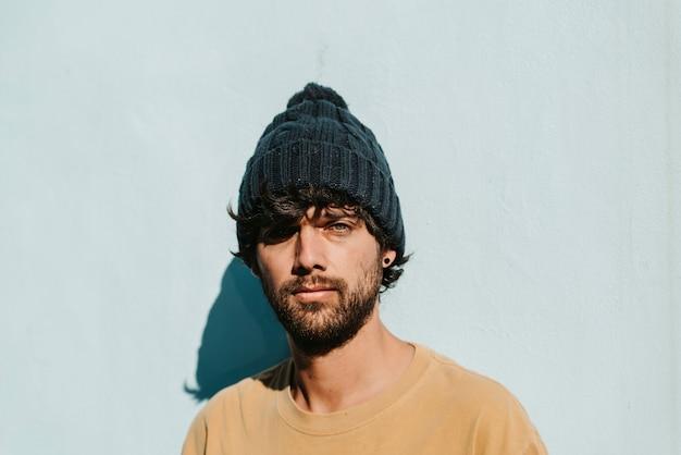 Een close-up portret van een jonge man met groene ogen met muts, baard en t-shirt.