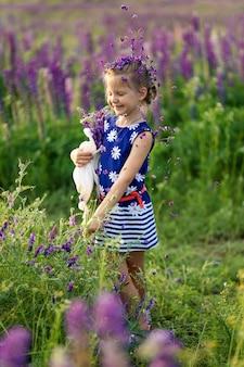 Een close-up portret van een klein schattig meisje met blond haar speelt op een bloeiende lupine veld. jeugd concept. kinderen en natuur.