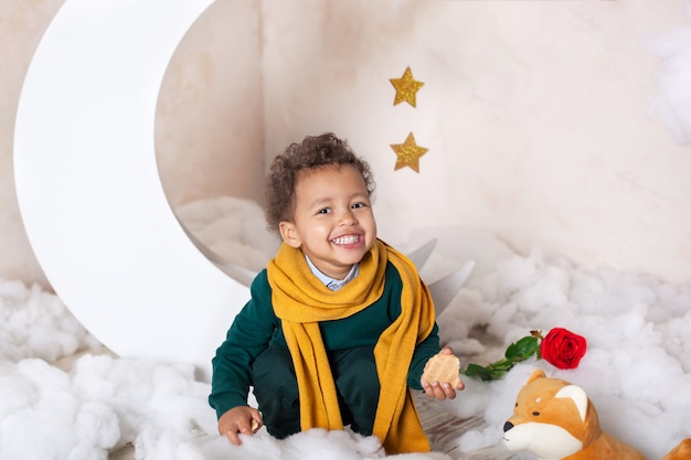 Een close-up portret van het gezicht van een afro-amerikaanse jongen. kleine jongen zit en glimlacht. schattige baby, baby in het spel. mooie lach. gekruld haar. kindertijd. kind speelt in de kleuterschool. child preschool education