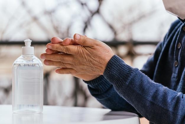 Een close-up shot van de handen van een man met behulp van een handdesinfecterend middel