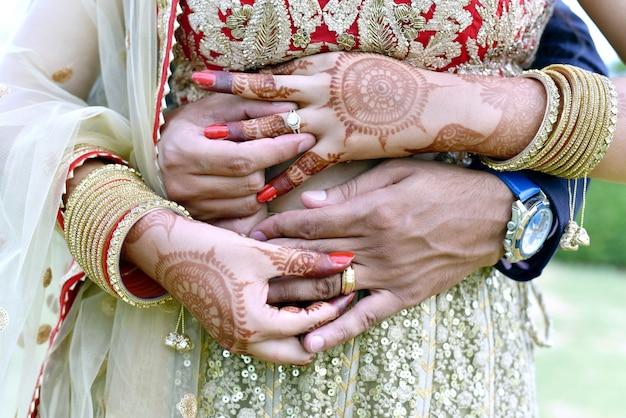 Een close-up shot van een jong stel dat knuffelt en hun trouwringen laat zien in india