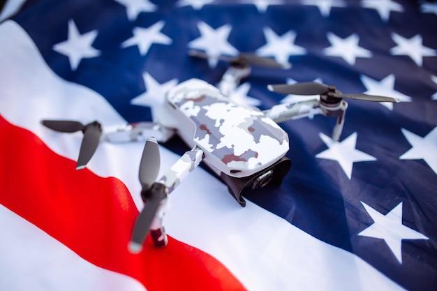 Een close-up shot van een liegende drone. de drone ligt op de amerikaanse vlag op een groen tarweveld.