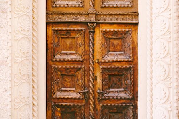 Een close-up van bruine deuren met opgeheven gravures en patronen in een witte gevormde opening