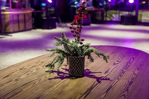 Een close-up van de decoratie met een bloem en een tak van een spar op tafel in het restaurant