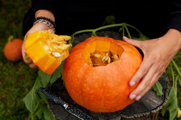 Een close-up van de hand van de mens snijdt een deksel van een pompoen terwijl hij een jack olantern voorbereidt. halloween. decoratie voor feest.
