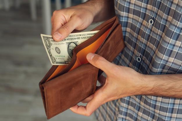 Een close-up van de hand van een man haalt een biljet van 1 dollar in zijn portemonnee