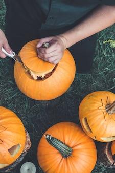 Een close-up van de hand van een man snijdt een deksel van een pompoen terwijl hij een hefboom-o-lantaarn voorbereidt. halloween. decoratie voor feest. bovenaanzicht. getinte foto.