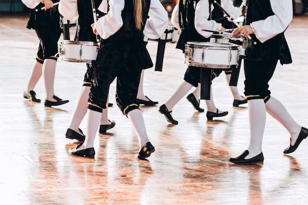 Een close-up van de handen van een drummer op een parade. kinderensemble in witte overhemden. witte nieuwe snaredrum, witte stokken. het concept van een militaire parade en mars.