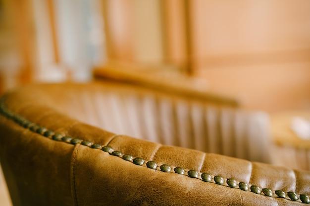 Een close-up van de rugleuning van de stoel, die verandert in een armleuning van bruin echt leer