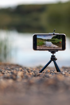 Een close-up van de telefoon op een statief maakt een video of een foto van de natuur. een prachtig meer in het bos met wolken in het scherm van de mobiele telefoon van de fotograaf.