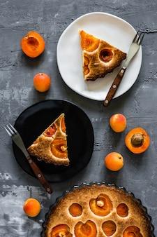 Een close-up van een abrikozentaart, een witte en een zwarte plaat met stukjes taart en vorken, abrikozen rond