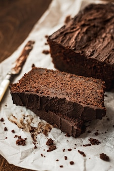 Een close-up van een gesneden chocoladetaart en een mes op bakpapier op donkere houten tafel