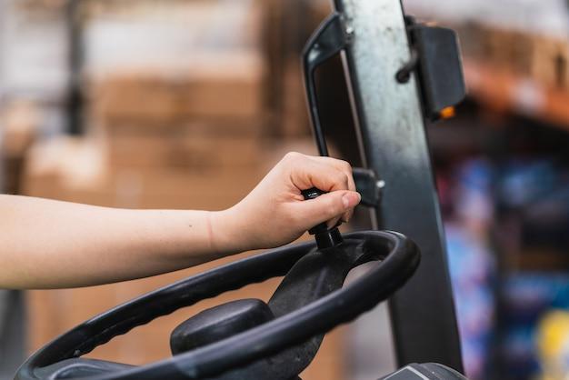 Een close-up van een hand op het stuur van een vorkheftruck