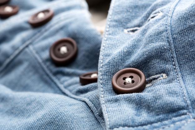 Een close-up van een jeansvest met plastic knopen