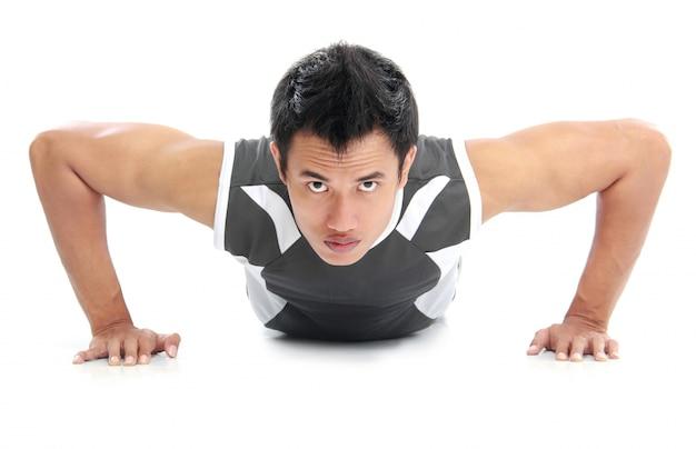 Een close up van een man die push-ups doet met een intense uitdrukking op zijn gezicht