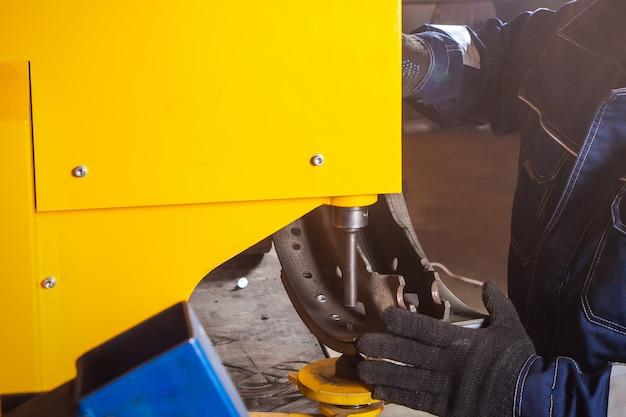 Een close-up van een man monteur klinkende rem