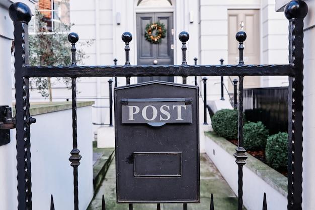 Een close-up van een oude roestige zwarte brievenbus dichtbij een huis met een onscherpe achtergrond