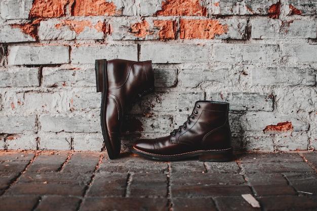Een close-up van een paar klassieke schoenen op een bakstenen muur