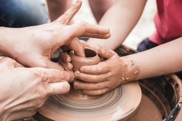 Een close-up van het keramische productieproces op een pottenbakkersschijf met kinderen kleiambachten met kinderen