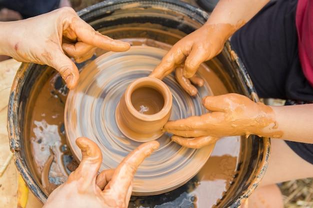 Een close-up van het keramische productieproces op een pottenbakkersschijf met kinderen