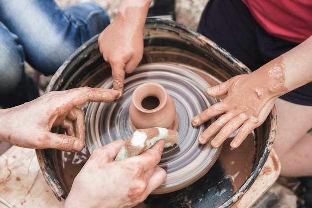 Een close-up van het keramische productieproces op het pottenbakkerswiel met kinderen kleiambachten met kind