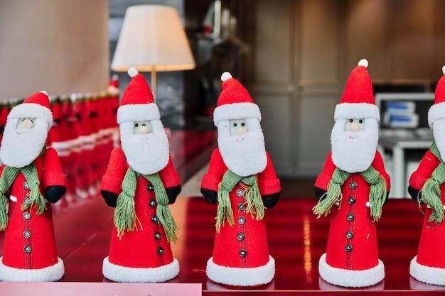Een close-up van klein speelgoed van de kerstman op de tafel onder de lichten met een wazige pagina