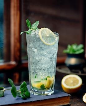 Een close up van mojito glas met citroen en ijs scheren
