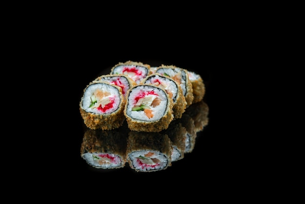 Een close up van voedsel gebakken sushi rolt geïsoleerd op zwarte reflectie