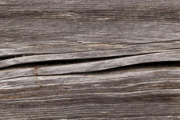 Een close-upfoto van een beschadigd houten oppervlak dat de muur is van een huis in het dorp. scheuren en verval van planken