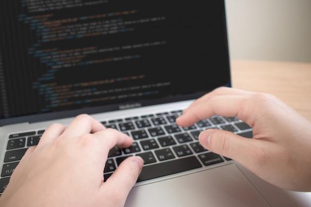 Een close-upfoto van een hand die in een programmeur werkt om sommige systemen te maken.