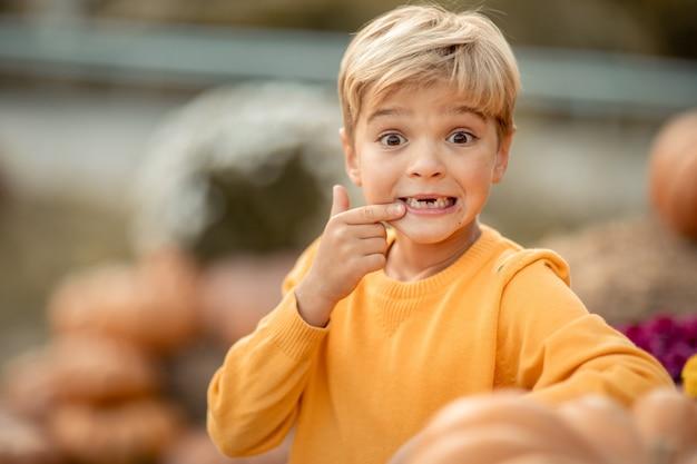 Een close-upjongen in een gele sweater dichtbij het pompoengewas.