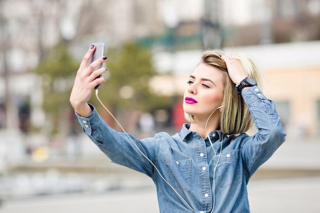 Een close-upportret van een dromerig blond meisje met felroze lippen die een selfie op een smartphone nemen