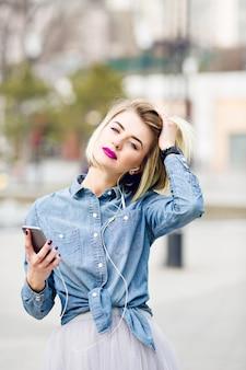 Een close-upportret van een dromerig blond meisje met felroze lippen, luisteren naar muziek op een smartphone