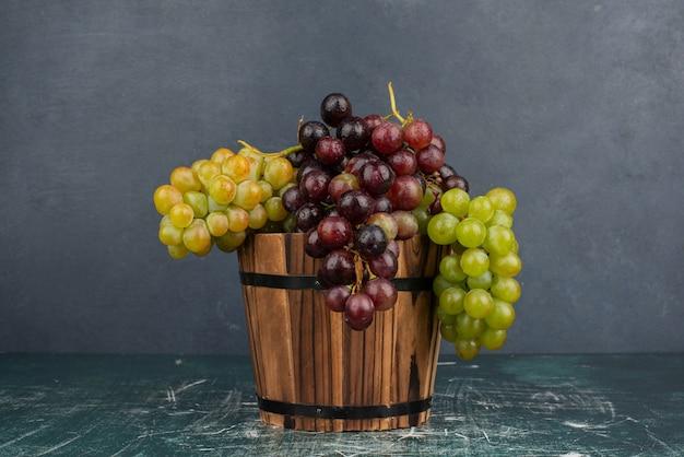 Een cluster van groene en zwarte druiven op marmeren tafel.