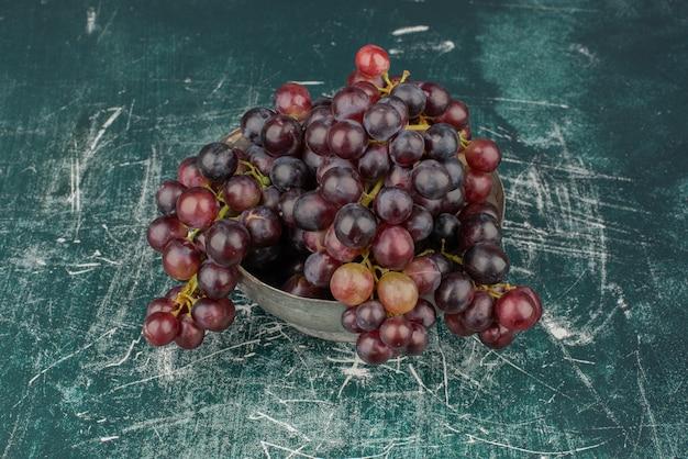 Een cluster van zwarte druiven in de vaas op marmeren tafel.