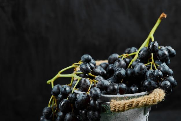 Een cluster van zwarte druiven in emmer op donkere ondergrond