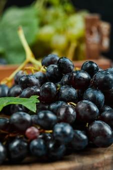 Een cluster van zwarte druiven op houten plaat, close-up
