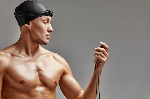 Een coach met een stopwatch in zijn handen, een sportzwemcoach met een timer in zijn handen, grijze achtergrond, kopieer ruimte.