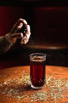 Een cocktail in een collins longdrinkglas met een ijsspeer, op een houten tafel, aan de bar. barman spuit een aromatische infusie op een cocktail