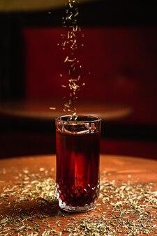 Een cocktail in een collins longdrinkglas met een ijsspeer, op een houten tafel, aan de bar. de cocktail besprenkelen met dennennaalden.