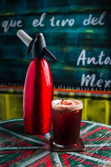 Een cocktail in een longdrinkglas met schuim, ijsblokje erin, gegarneerd met een limoenwiel en granaatappelpitjes